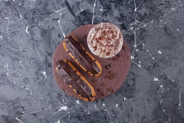 Pyszne słodkie czekoladowe eklery i filiżanka kawy na kawałku drewna.