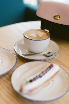 Pyszne słodkie francuskie eklery i kawa w kawiarni