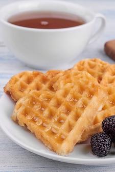 Pyszne słodkie gofry belgijskie w formie serc z miodem i herbatą na niebieskim drewnianym stole. śniadanie.