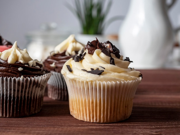 Pyszne słodkie ręcznie robione babeczki czekoladowe na drewnianym stole. wykwintne wyroby cukiernicze. przedni widok