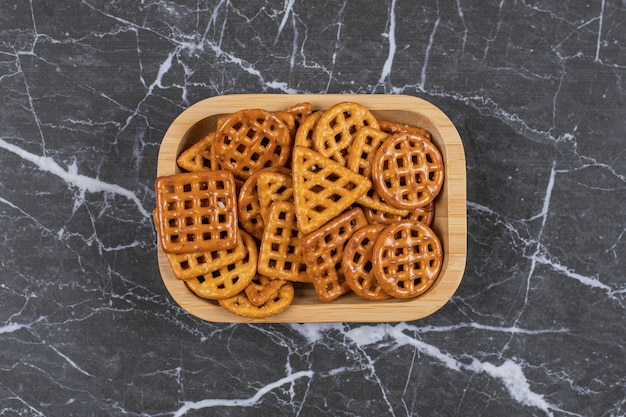 Pyszne słone krakersy na drewnianym talerzu.