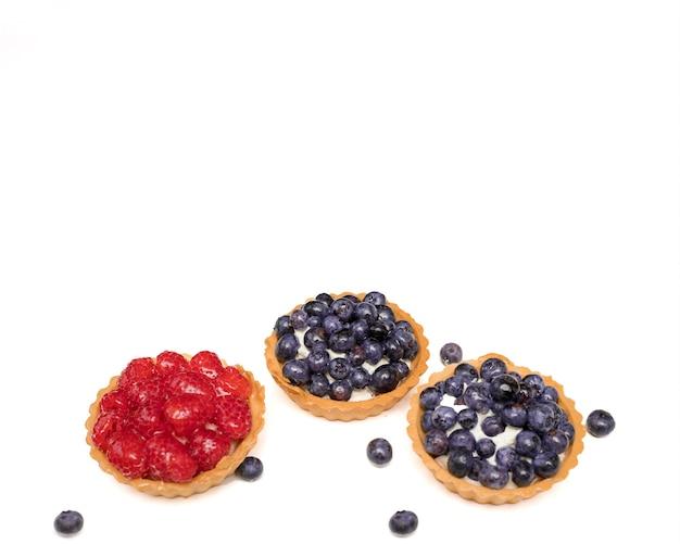 Pyszne, smaczne świeże deserowe koszyczki z kruchego ciasta ozdobione świeżymi jagodami i malinami wśród kwiatów. koncepcja pieczenia piekarni, słodyczy. zdjęcie z bliska. na białym tle, kopia przestrzeń