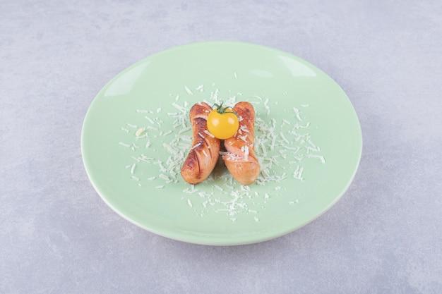 Pyszne smażone kiełbaski i pomidorki koktajlowe na zielonym talerzu.