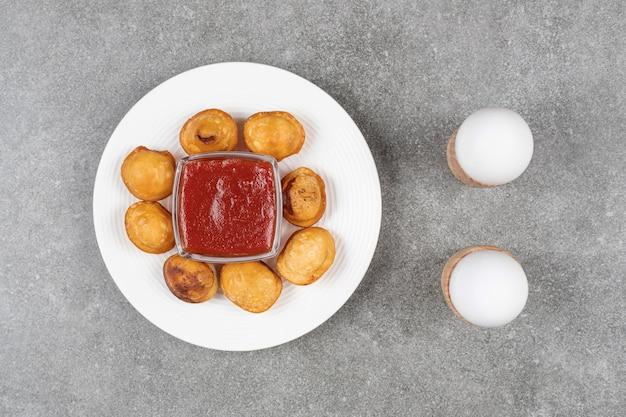 Pyszne smażone pierogi na białym talerzu z keczupem