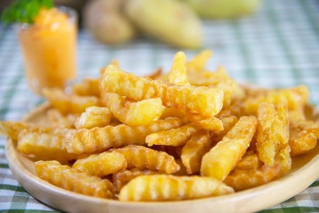 Pyszne smażone ziemniaki na drewnianej tablicy z maczanym sosie - tradycyjna koncepcja fast food