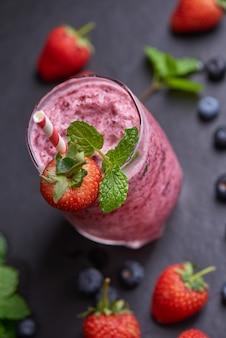 Pyszne smoothie z truskawek, morwy i jagód przyozdobione świeżymi jagodami i miętą w szkle. nieostrość. piękne różowe maliny przekąska, dobre samopoczucie i koncepcja odchudzania.