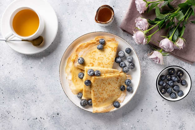Pyszne śniadanie. cienkie naleśniki, filiżanka herbaty, jagody i bukiet róż