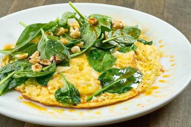 Pyszne śniadanie - francuska jajecznica ze szpinakiem, serem brie, orzechami laskowymi i pikantną oliwą z oliwek w białym talerzu na drewnianej powierzchni. zbliżenie, selektywne skupienie