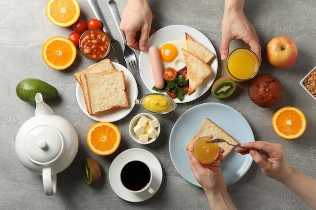 Pyszne śniadanie lub lunch. szary stół. ludzie jedzą