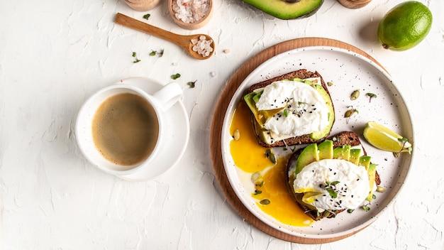 Pyszne śniadanie lub przekąska z jajkiem gotowanym na awokado i filiżanką kawy na jasnej powierzchni, widok z góry