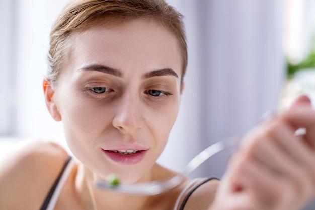Pyszne śniadanie. miła młoda kobieta patrząc na widelec jedząc posiłek