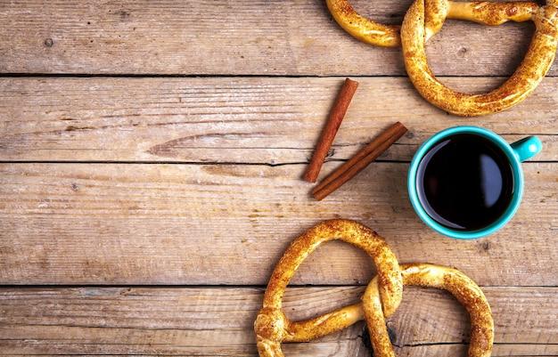 Pyszne śniadanie, precel z kawą na podłoże drewniane. jedzenie, napoje. i