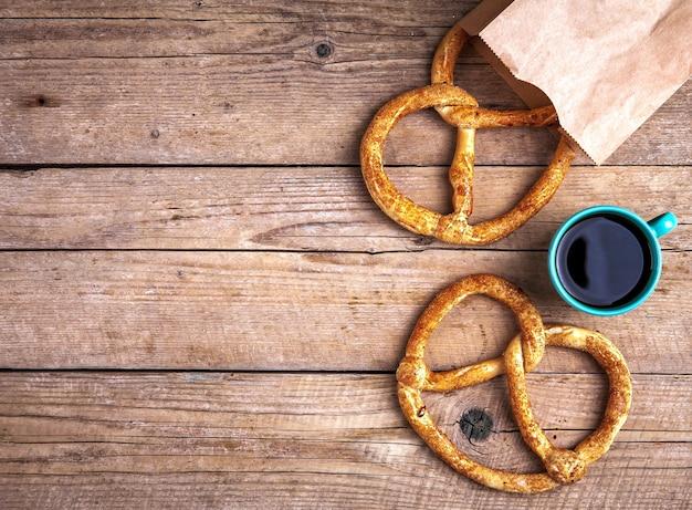 Pyszne śniadanie, precel z kawą na podłoże drewniane. jedzenie, napoje.