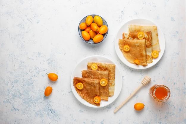 Pyszne śniadanie. święto prawosławne maslenica. naleśniki z cumquats i honet, widok z góry