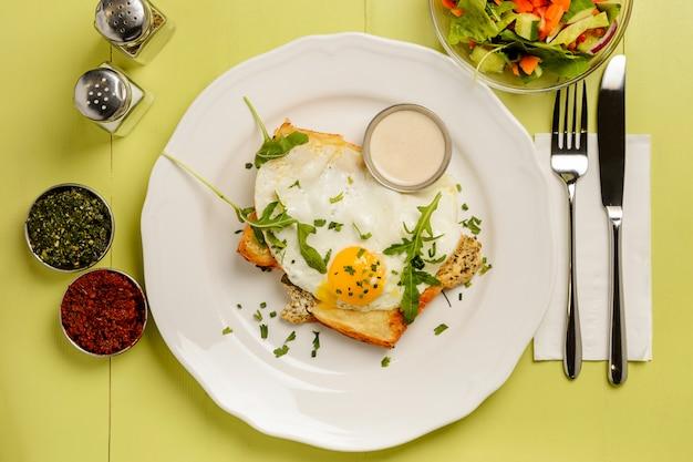 Pyszne śniadanie. tost z jajkiem, sałatką i przyprawami