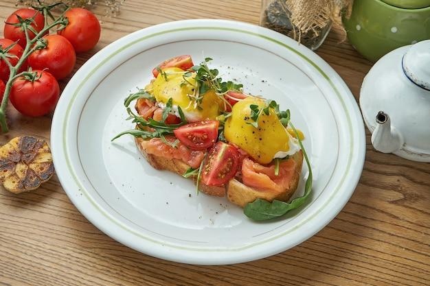 Pyszne śniadanie - tost z łososiem, jajko w koszulce z sosem holenderskim i pomidorkami koktajlowymi, podane na białym talerzu.