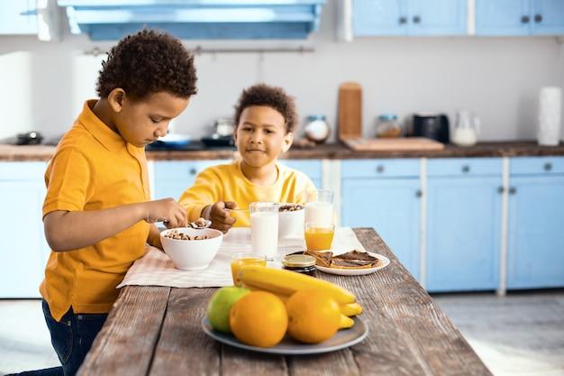 Pyszne śniadanie. uroczy mały chłopiec stojący przy stole i jedzący płatki śniadaniowe razem ze swoim starszym bratem