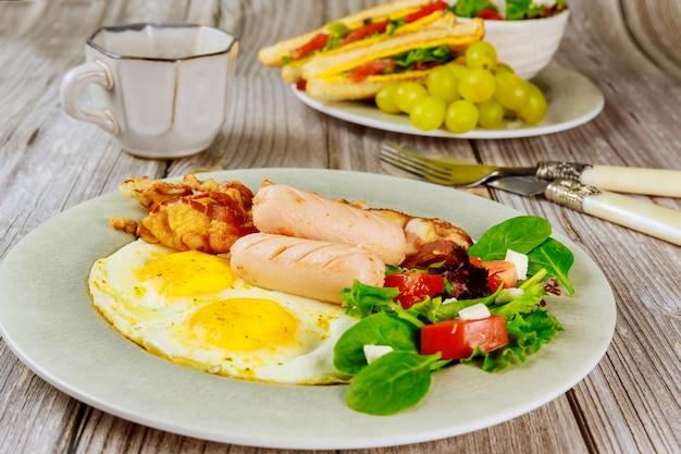 Pyszne śniadanie z jajkami, kiełbasami, boczkiem i filiżanką kawy