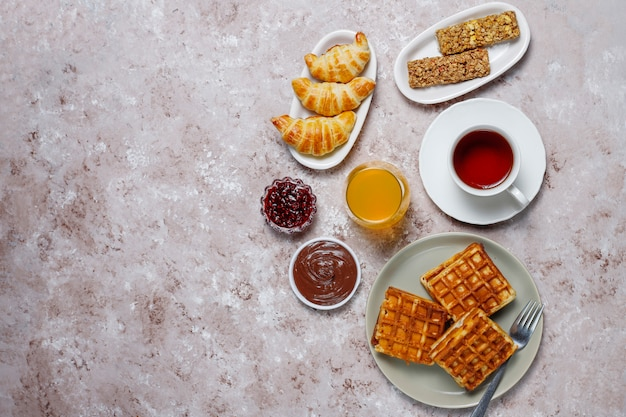 Pyszne śniadanie z kawą, sokiem pomarańczowym, goframi, rogalikami, dżemem, pastą orzechową na świetle, widok z góry