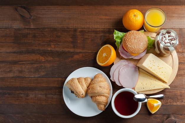 Pyszne śniadanie z rogalikami, kanapkami i sokiem pomarańczowym