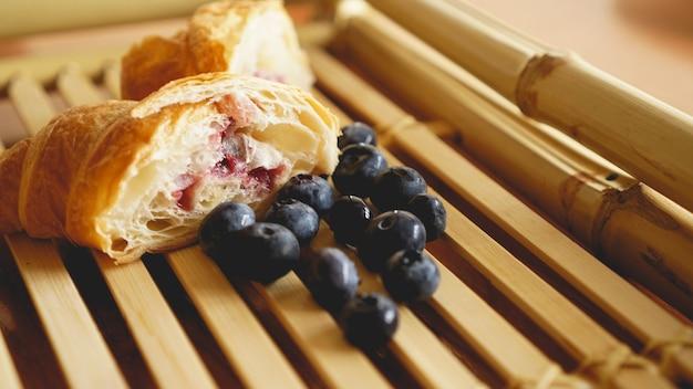 Pyszne śniadanie ze świeżym croissantem i jagodami na drewnianym tle