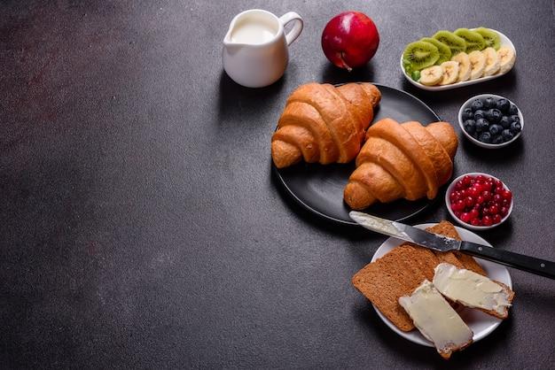 Pyszne śniadanie ze świeżymi rogalikami i dojrzałymi jagodami na pięknym drewnianym stole