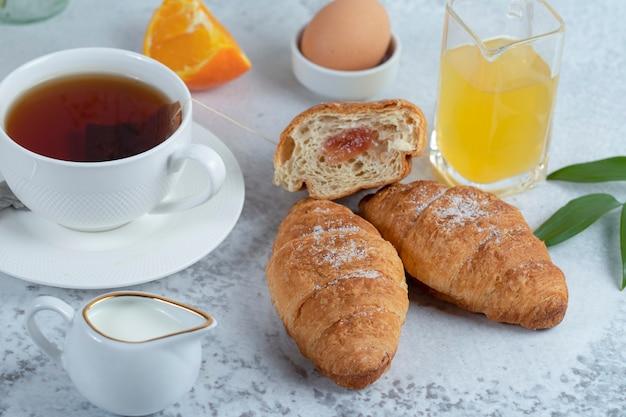 Pyszne śniadanie ze świeżymi rogalikami i filiżanką czarnej gorącej herbaty.