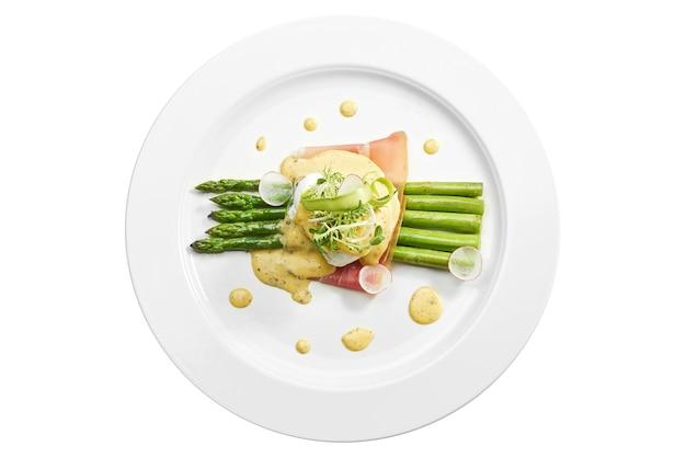 Pyszne śniadaniowe szparagi z jajkiem w koszulce, boczkiem, sosem holenderskim w białym talerzu. na białym tle na białej powierzchni. widok z góry