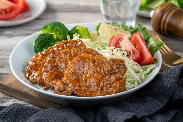 Pyszne soczyste kotlety wieprzowe z warzywami w talerzu na stole.