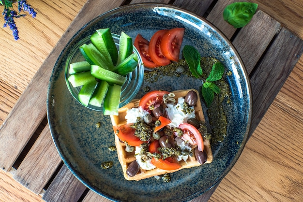 Pyszne, solone gofry belgijskie z suszonymi pomidorami i oliwkami kalamata na zielonym talerzu
