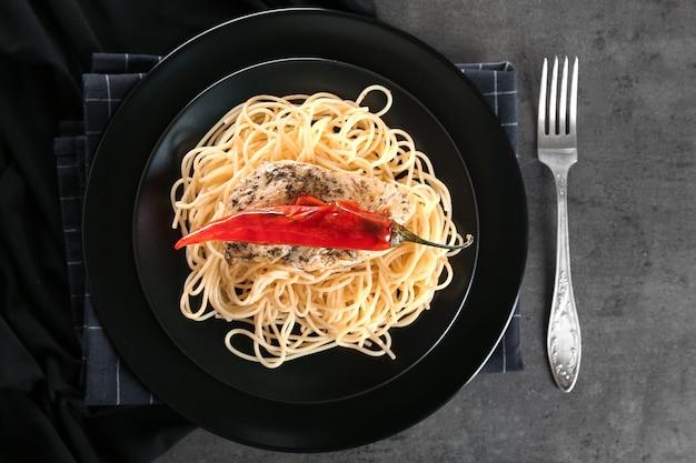 Pyszne spaghetti z kurczakiem z pieprzem na czarnym talerzu