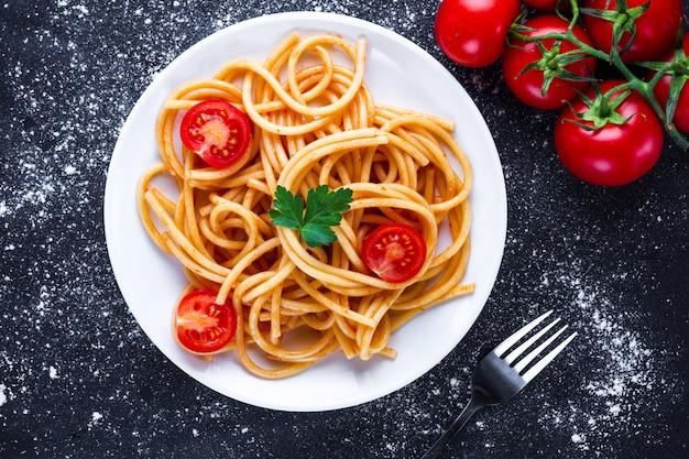 Pyszne spaghetti z natką pietruszki, pomidorkami i sosem pomidorowym na talerzu. włoskie jedzenie i makaron. widok z góry