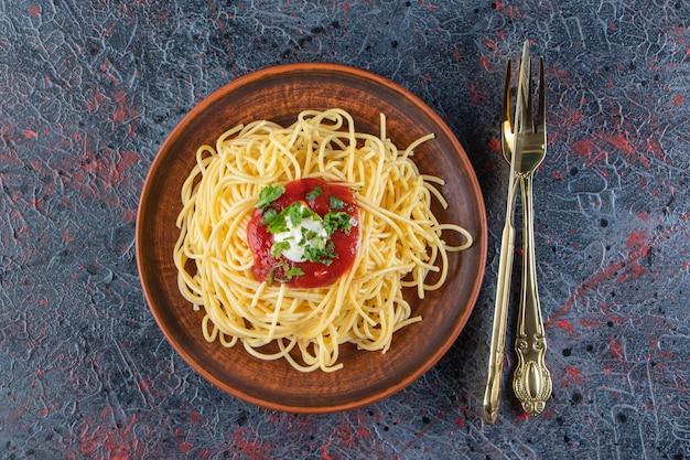Pyszne spaghetti z sosem pomidorowym na drewnianym talerzu ze sztućcami.