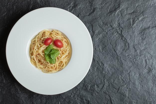 Pyszne spaghetti z zieleniną i pomidorkami koktajlowymi.