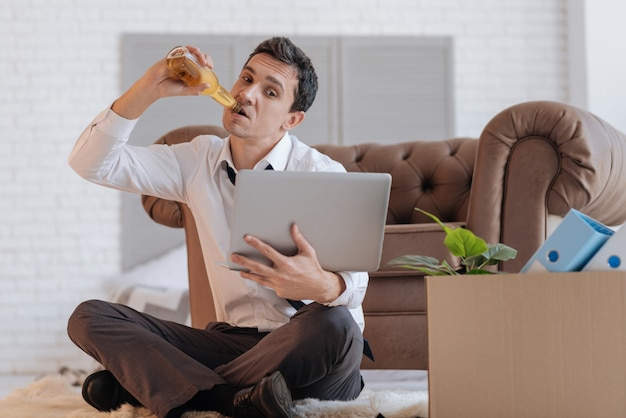 Pyszne. spokojny, uważny młody bezrobotny patrząc na ekran swojego laptopa, siedząc na podłodze ze skrzyżowanymi nogami i pijąc alkohol z butelki