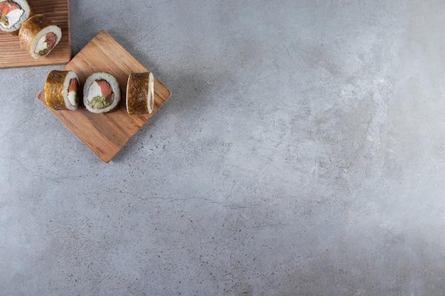 Pyszne sushi rolki z tuńczykiem i sosem sojowym na kamiennym tle.