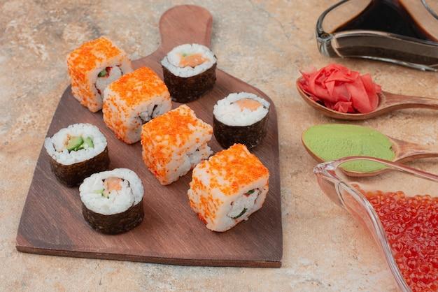 Pyszne sushi z kawiorem, imbirem i wasabi na drewnianym talerzu