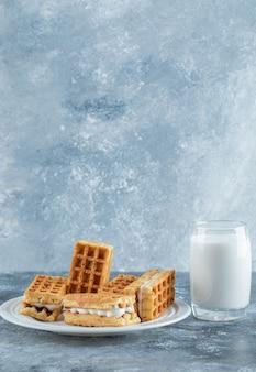 Pyszne świeże gofry ze szklanym kubkiem mleka.