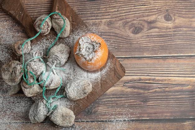 Pyszne świeże i suszone owoce persimmon na drewnianej desce
