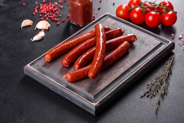 Pyszne świeże jasne wędzone gorące kiełbaski z pomidorkami cherry i sosem pomidorowym na ciemnym betonowym stole