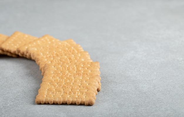Pyszne świeże krakersy na szarym tle.