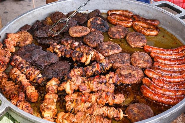 Pyszne świeże mięso smażone jest na dużej patelni w ulicznej kawiarni.