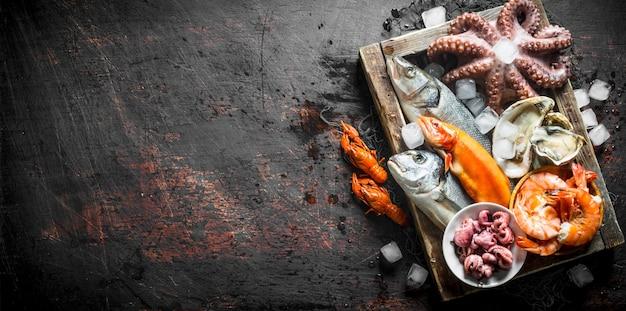 Pyszne świeże owoce morza na drewnianej tacy z lodem na ciemnym stole rustykalnym