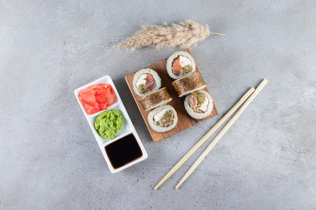 Pyszne świeże sushi z sosem sojowym i drewnianymi pałeczkami umieszczonymi na drewnianej desce.