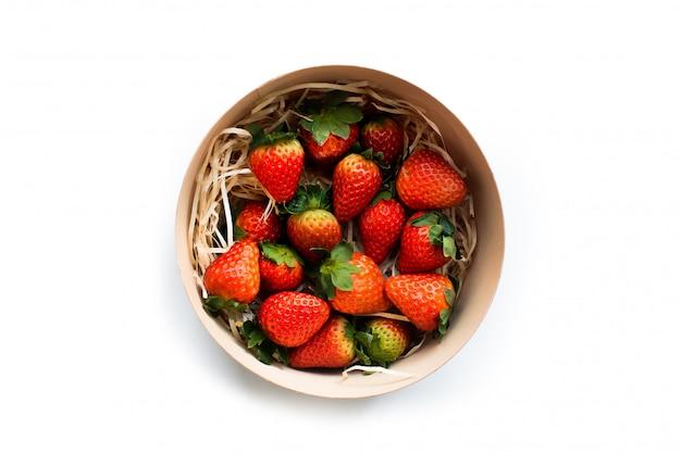 Pyszne świeże truskawki w okrągłym drewnianym pudełku, widok z góry