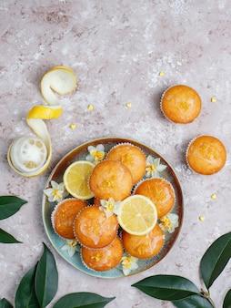 Pyszne świeżo upieczone domowe babeczki cytrynowe z cytrynami na talerzu na stole