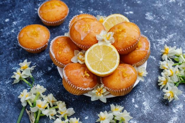 Pyszne, świeżo upieczone domowe babeczki cytrynowe z cytrynami na talerzu
