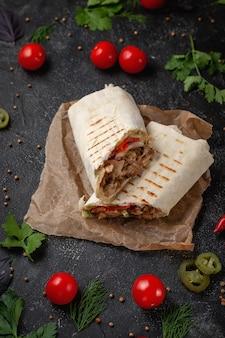 Pyszne tacos shawarma i lavash na ciemnym kamiennym stole. restauracja fast food. zdrowa opcja fast foodów. smaczne świeże zawijane kanapki z mięsem wołowym i warzywami, tradycyjna przekąska z bliskiego wschodu