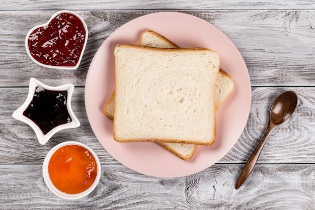 Pyszne tosty na różowym talerzu ze słodkimi dżemami i zalesioną łyżką na drewnianym stole.