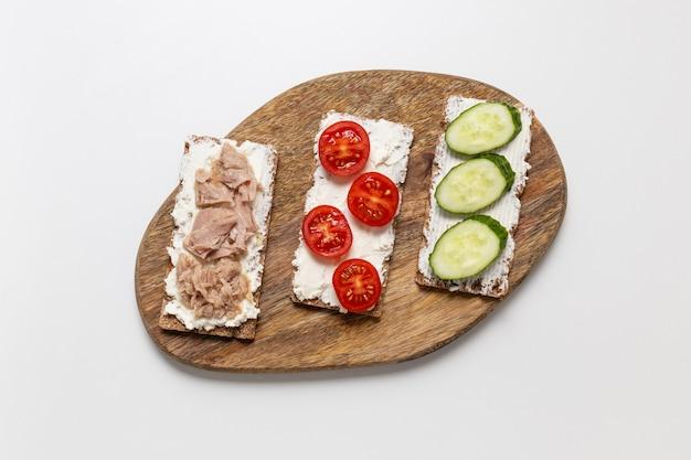 Pyszne tosty z chrupiącym pieczywem z różnymi nadzieniami na stole. ogórek, pomidor, serek i tuńczyk to składniki kanapek.